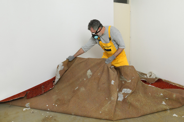 man tearing out damaged carpet